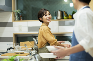 食器を洗いながら会話する男女の写真素材 [FYI04789546]