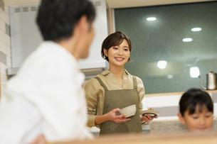 料理を配膳する母親と家族の写真素材 [FYI04789560]