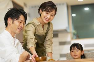 料理を配膳する母親と家族の写真素材 [FYI04789561]