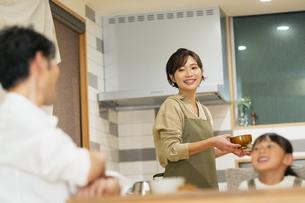 料理を配膳する母親と家族の写真素材 [FYI04789562]