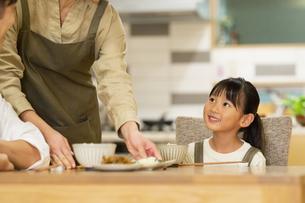 料理を配膳する母親と家族の写真素材 [FYI04789563]