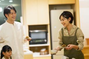 料理を配膳する家族の写真素材 [FYI04789565]