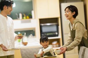 料理を配膳する家族の写真素材 [FYI04789567]