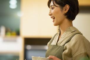 料理を配膳するエプロン姿の女性の写真素材 [FYI04789568]