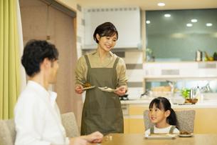 料理を配膳する家族の写真素材 [FYI04789570]