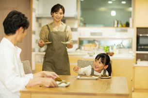 料理を配膳する家族の写真素材 [FYI04789572]