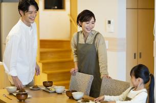 料理を配膳する家族の写真素材 [FYI04789576]