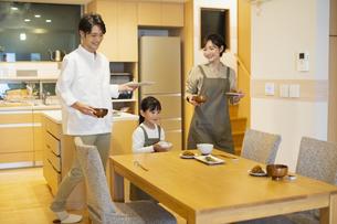 料理を配膳する家族の写真素材 [FYI04789577]