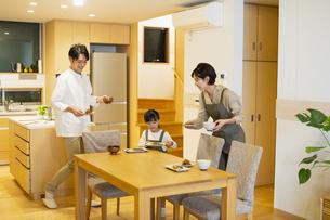 料理を配膳する家族の写真素材 [FYI04789579]