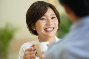 部屋でコップを持ちながら会話する男女の写真素材 [FYI04789582]