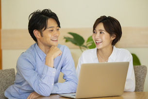 部屋でパソコンを見ながら会話する男女の写真素材 [FYI04789583]