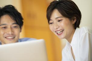 部屋でパソコンを見ながら会話する男女の写真素材 [FYI04789585]