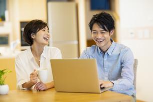 部屋でパソコンを見ながら会話する男女の写真素材 [FYI04789589]