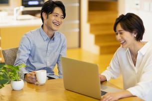 部屋でパソコンを見ながら会話する男女の写真素材 [FYI04789590]