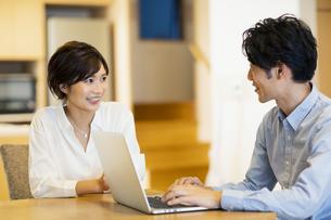 部屋でパソコンを見ながら会話する男女の写真素材 [FYI04789591]