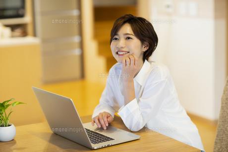 部屋でパソコンを見ながら楽しそうな女性の写真素材 [FYI04789593]