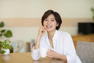 部屋でコップを持つ笑顔の女性の写真素材 [FYI04789594]