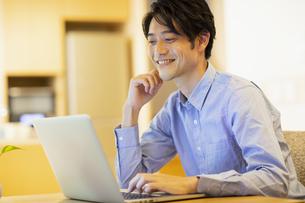 部屋でパソコンを見ながら楽しそうな男性の写真素材 [FYI04789595]