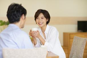 部屋でコップを持ちながら会話する男女の写真素材 [FYI04789596]