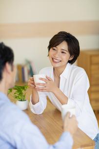 部屋でコップを持ちながら会話する男女の写真素材 [FYI04789597]