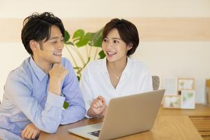 部屋でパソコンを見ながら会話する男女の写真素材 [FYI04789599]