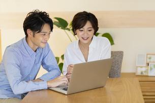 部屋でパソコンを見ながら会話する男女の写真素材 [FYI04789600]