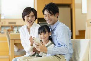 ソファーでスマートフォンを見ながらくつろぐ家族の写真素材 [FYI04789606]