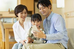 ソファーでスマートフォンを見ながらくつろぐ家族の写真素材 [FYI04789607]