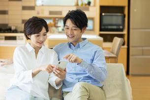 ソファーでスマートフォンを見る男女の写真素材 [FYI04789608]