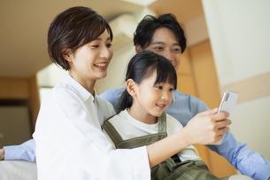 部屋でスマートフォンを見ながらくつろぐ家族の写真素材 [FYI04789612]