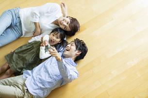 フローリングに寝転ぶ笑顔の家族の写真素材 [FYI04789617]