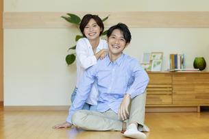 フローリングに座る笑顔の男女の写真素材 [FYI04789622]