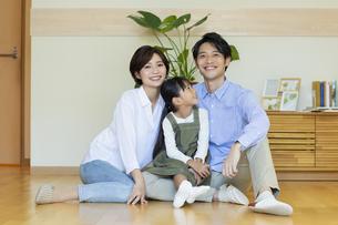 フローリングに座る笑顔の家族の写真素材 [FYI04789625]