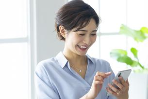 窓際でスマートフォンを操作する女性の写真素材 [FYI04789635]