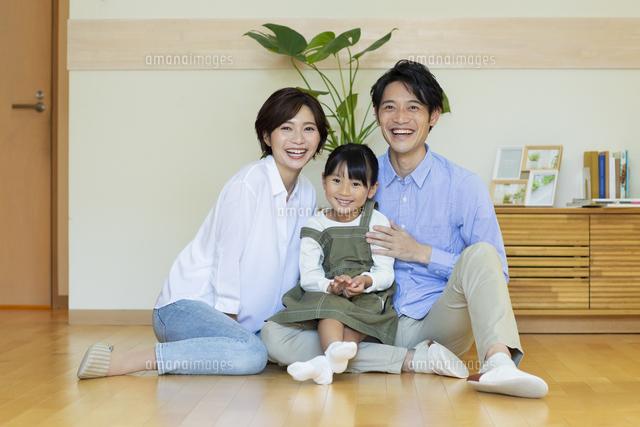 フローリングに座る笑顔の家族の写真素材 [FYI04789666]