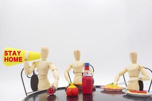 会食をしながらメガホンで外出自粛を呼びかけるデッサン人形の写真素材 [FYI04791339]