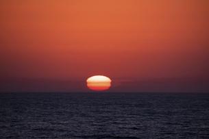 水平線に沈む四角い夕陽の写真素材 [FYI04791871]