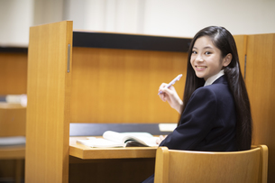 個室で勉強中に振り返る高校生の写真素材 [FYI04793099]