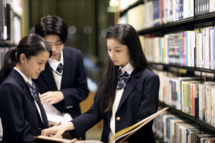 図書室で立ちながら本を読む高校生の写真素材 [FYI04793100]