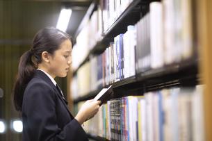 図書室で本を読む女子高校生の写真素材 [FYI04793101]