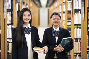 図書室で本を持って微笑む二人の女子高校生の写真素材 [FYI04793103]