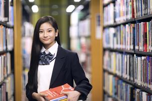 図書室で本を持って微笑む女子高校生の写真素材 [FYI04793104]