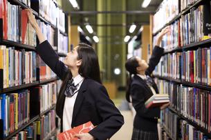 図書室で本を手に取る高校生の写真素材 [FYI04793105]