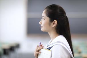 教室で立つ女子高校生の横顔の写真素材 [FYI04793117]