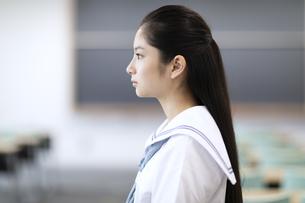 教室で立つ女子高校生の横顔の写真素材 [FYI04793119]