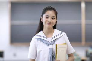 教室で微笑む女子高校生のポートレートの写真素材 [FYI04793120]