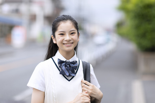前を向いて微笑む女子高校生のポートレートの写真素材 [FYI04793123]