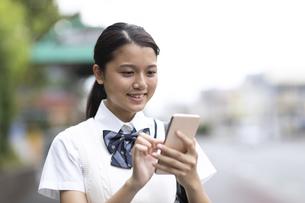 スマートフォンを操作する女子高生の写真素材 [FYI04793130]