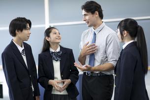 外国人教師と会話する高校生の写真素材 [FYI04793132]