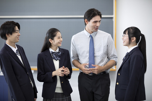 外国人教師と会話する高校生の写真素材 [FYI04793133]